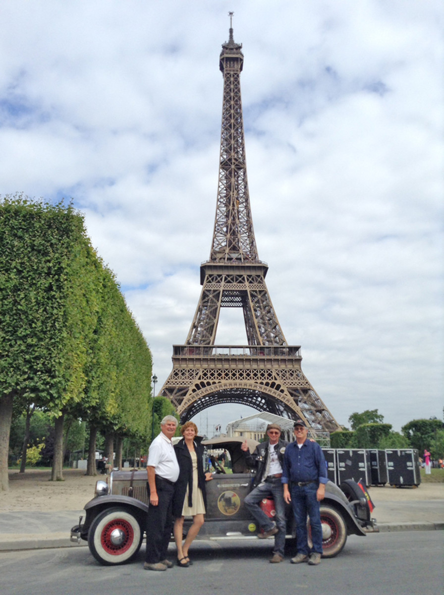John Quam (second from right) and his party leans against his 1928 Plymouth at the Eiffel Tower in Paris on Bastille Day.