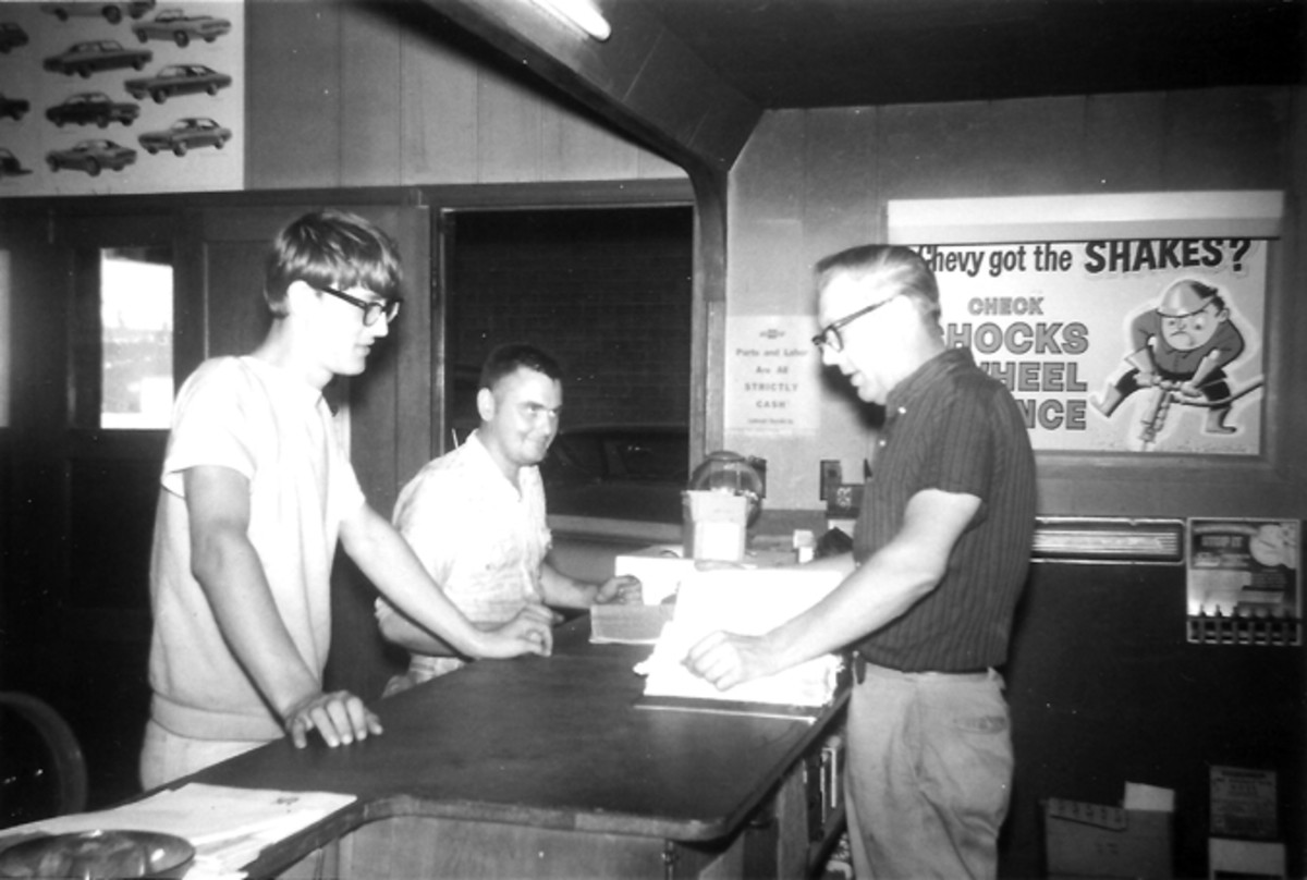 Ray Lambrecht talks with son Mark and a mechanic in his shop in 1970.