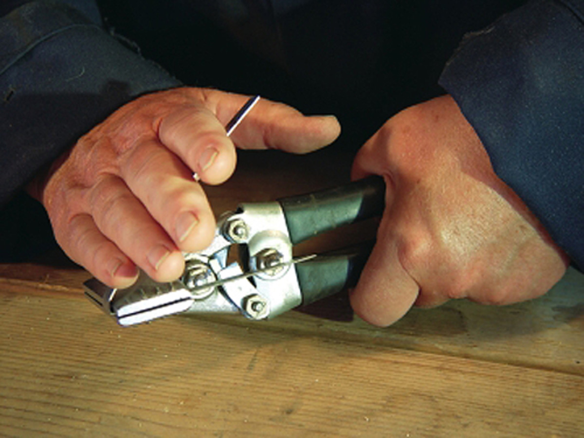 The metal is placed in the pliers and bent by hand as close to the pliers' jaws as possible.