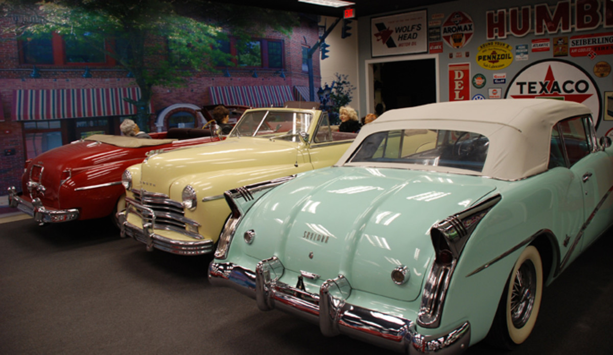Period signs complement these postwar drop tops, including a 1954 Buick Skylark, 1949 Plymouth and 1949 De Soto.