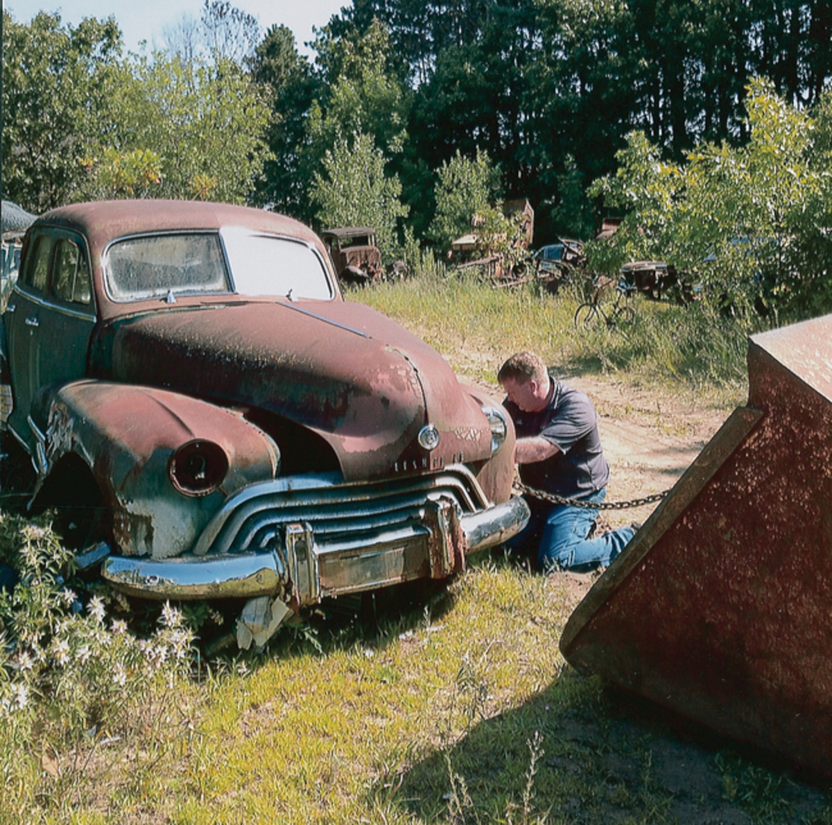 Luke Goedert of Cherry Valley Auto in Millville, Iowa, hooks a chain from his newly purchased 1948 Oldsmobile Dynamic sedan to a front-end loader to pull the car onto his trailer. Goedert plans to build the Olds into a rat rod.