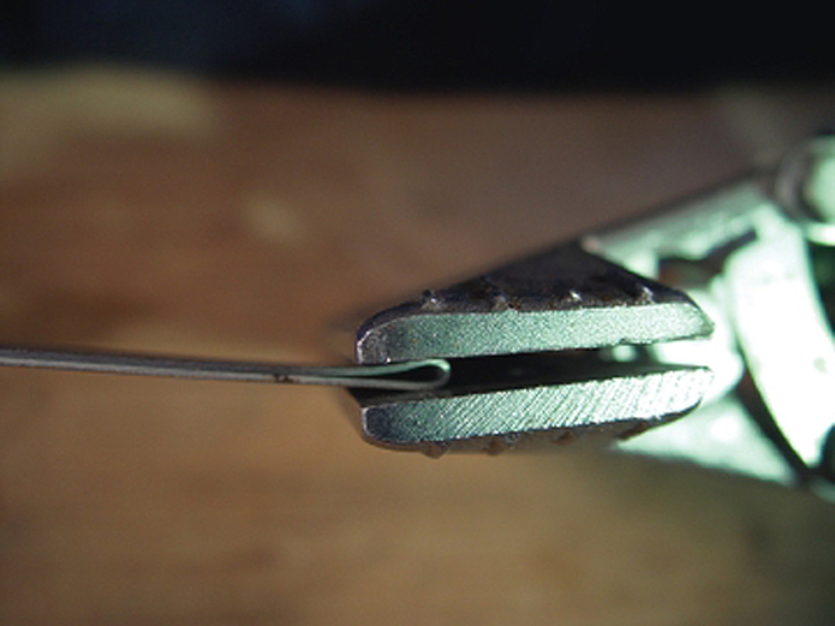 Now the metal is gripped between the pliers' jaws and compressed slightly.