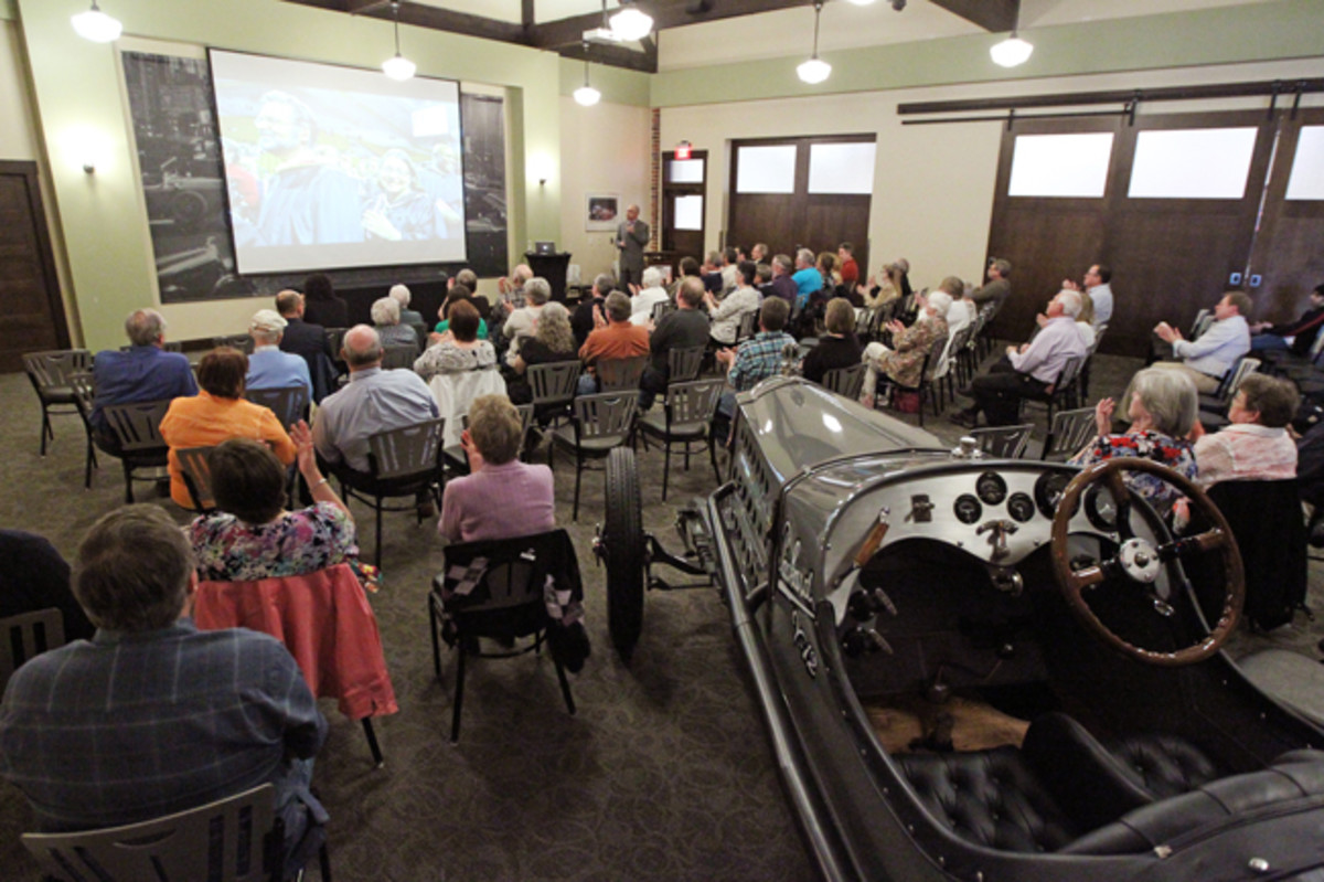 A crowd, sitting amongst a 1916 Packard racer, is enjoying a recent special lecture at the Gilmore Car Museum's speaker series.