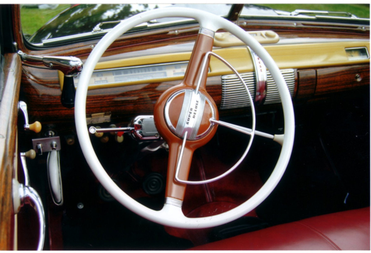 The interior of the car is like new. The Super Deluxe used a two-spoke steering wheel with a half-circle horn ring.