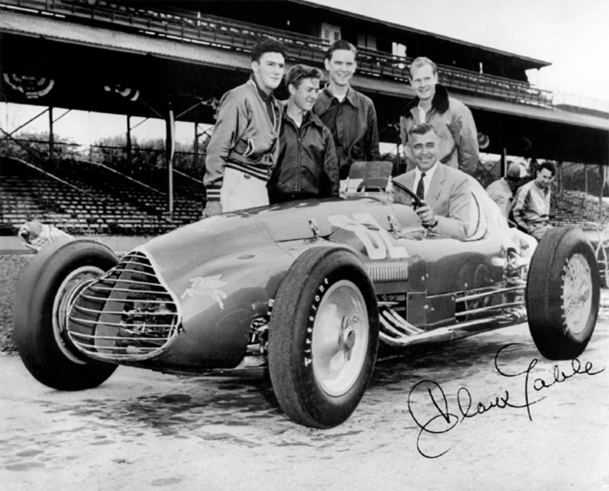 The story behind this picture: The Bob Estes team had an interesting encounter at Indianapolis in 1950 with screen legend Clark Gable, who happened to be at the Speedway while filming the Indianapolis-themed race drama, To Please a Lady. He posed for a photograph behind the wheel of the Bob Estes Special, including Estes team members Jack Doulin, Joe James, Jud Phillips, and Dick Ford, with Henry Banks, the AAA National Champion, sitting atop the wall in the background.