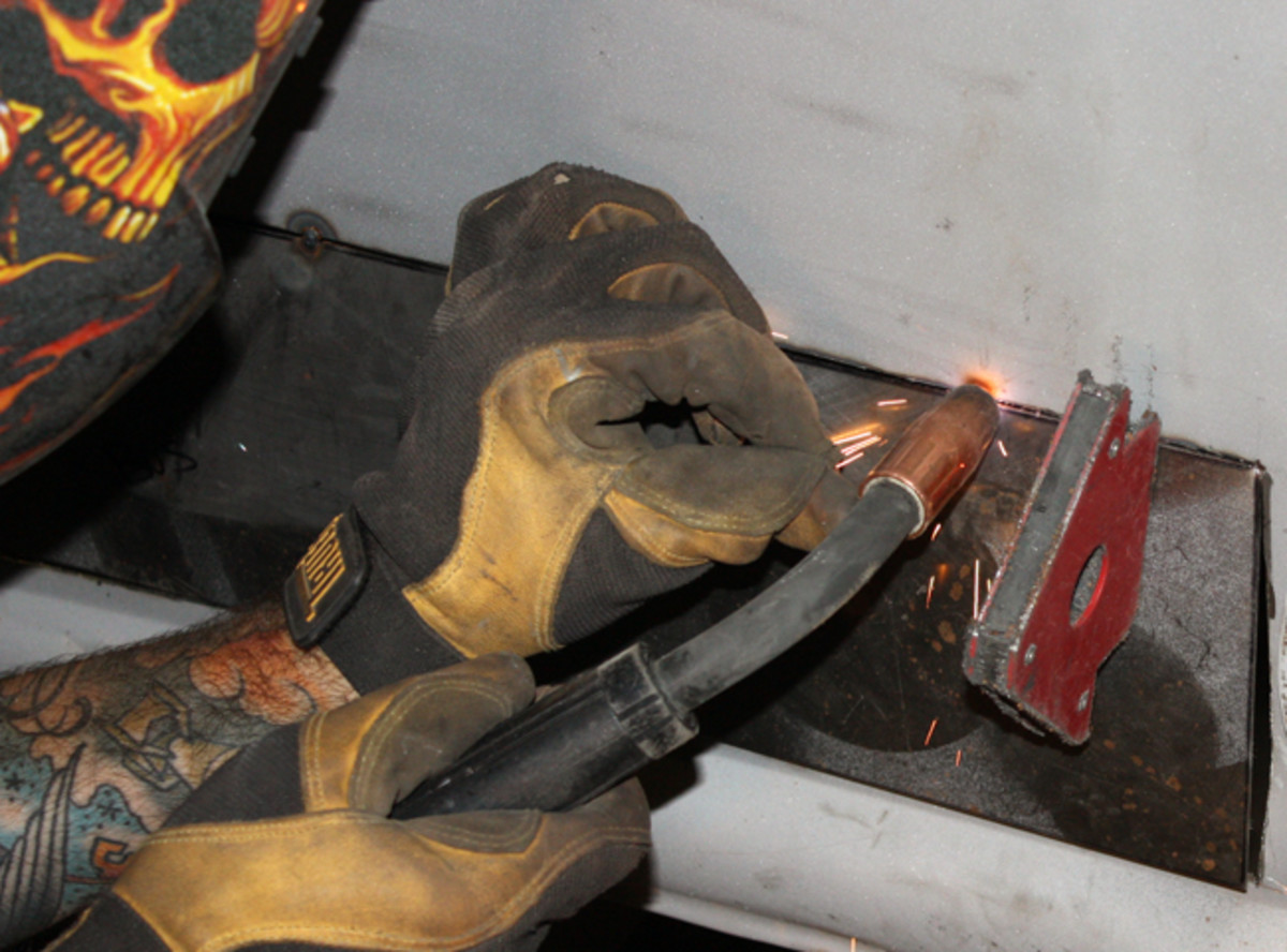 "Magnets are used to hold the patch panel in place while it is tack welded. The initial welds are made several inches apart by Fast Freddie's bodyman Peter Schnoor. He then welds all the way around the panel, alternating locations so the metal doesn't become overheated. Compressed air is used immediately after each weld to ""purge"" the weld and keep warping to a minimum. ""You can tell when it gets just a little too hot, and when you hit it with cold air, you can actually watch it pull back out,"" Schnoor noted. ""On an open panel like this, you're always going to have a little bit of warping or shrinkage, but it's nice to try to control it as much as possible."""