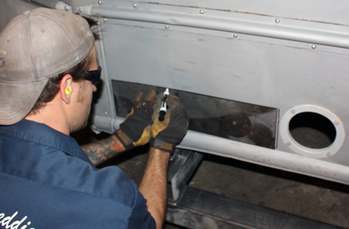 "A rectangular patch will be placed over this rusted area. In this case, a piece of tagboard was used as a template, which was then transferred to a piece of 18-gauge cold rolled steel. A cutting wheel is used to cut out the bad metal on the outside sheet metal of the bus. In this case, there is also an inside rocker panel, or ""fender skirt"" that will have to be addressed."