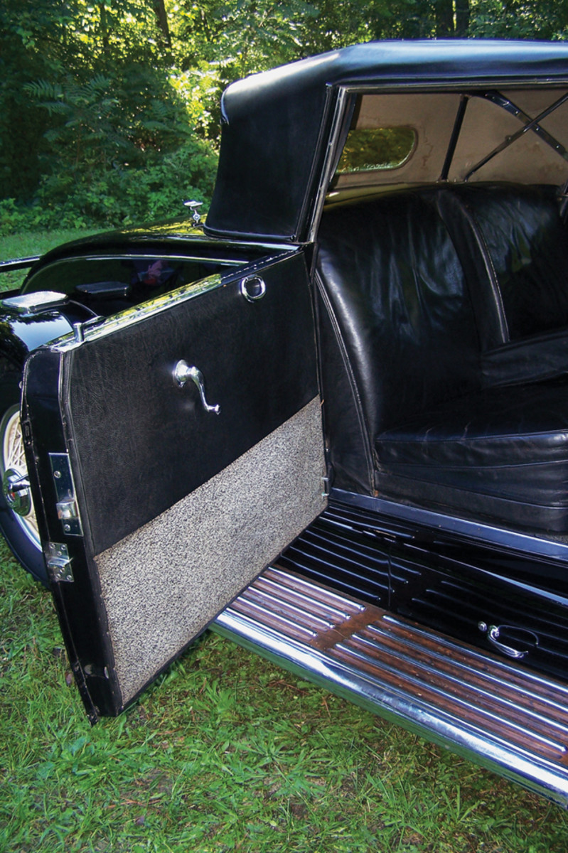 The interior is very original, down to the pepper-pattern upholstery on the bottom of the doors. This upholstery was fitted to all early Duesenberg Murphy convertible coupes built for showroom stock. The door construction also helps separate disappearing-top Murphy convertible coupes from non-disappearing-top models, such as this one. On this car, the door handle is at the very top of the door, and the top half of the door panel is upholstered with material. On disappearing top models, the door handle is on the panel, much like the window crank, and wood covers the upper half of the door panel.