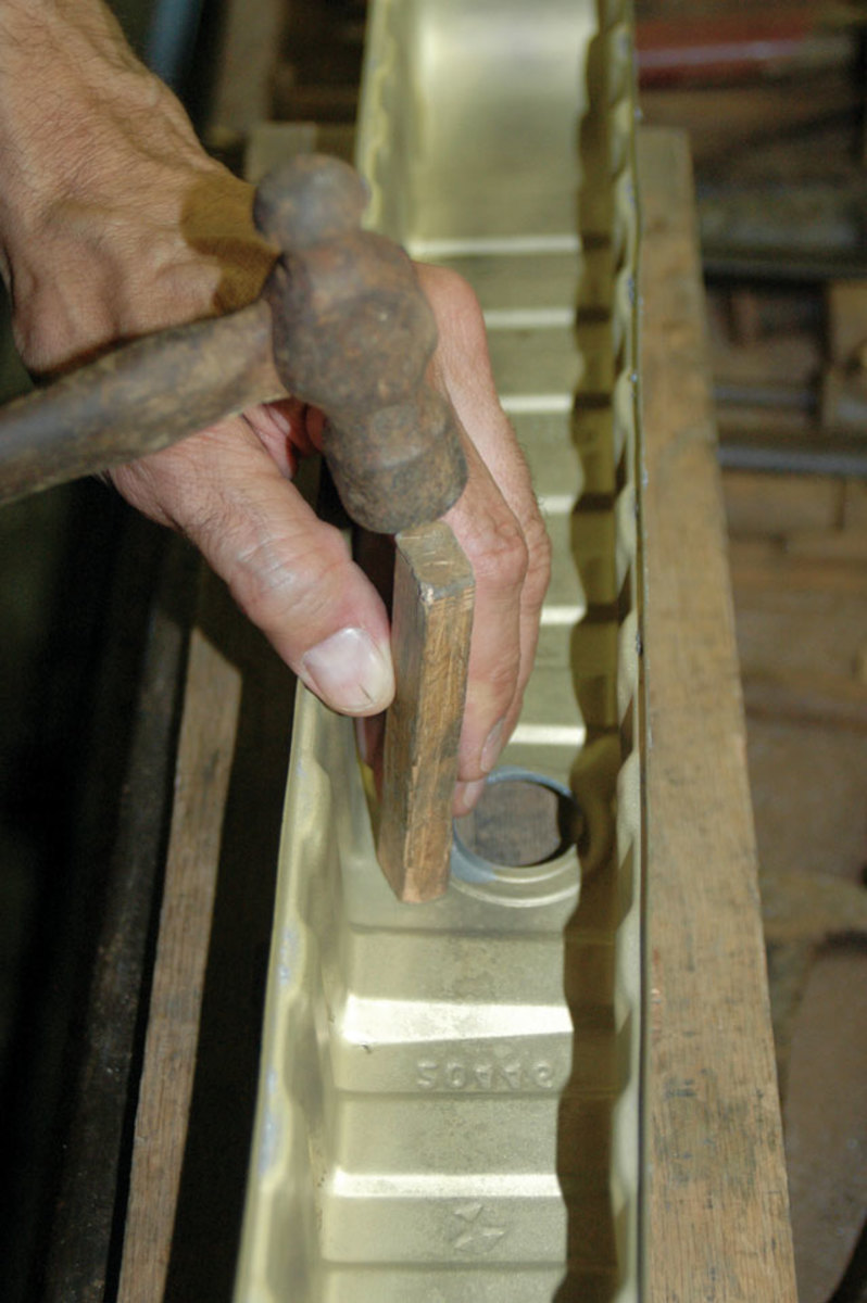Schirmer does all the de-denting and finishing on the repaired Hemi radiator tanks. He has a variety of small wooden blocks that he uses to tap out the dents on the tanks.