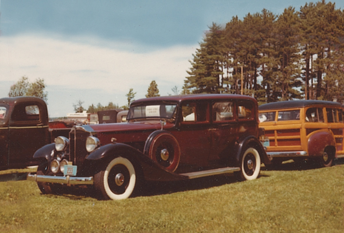 A regal 1933 Packard sedan basked in the park of one of the earliest car shows. Take note of the woodie and 1940s truck surrounding it.