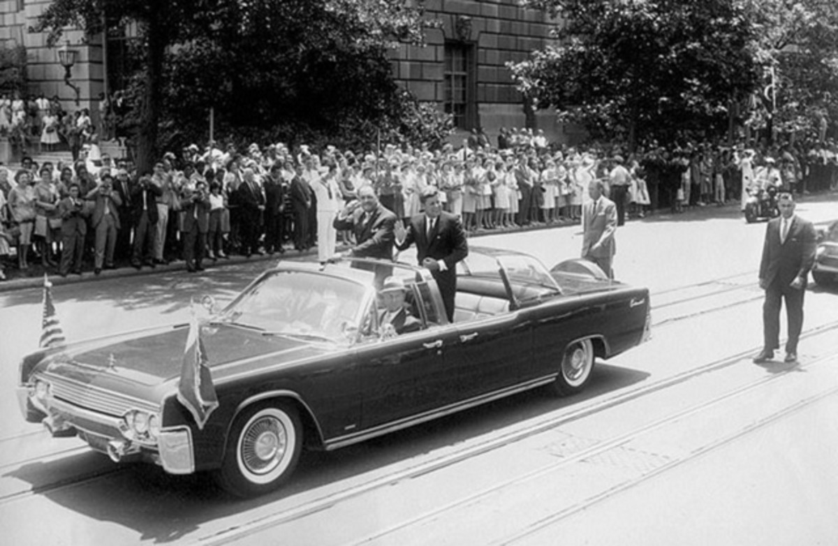 JFK standing in the SS-100-X during a procession.