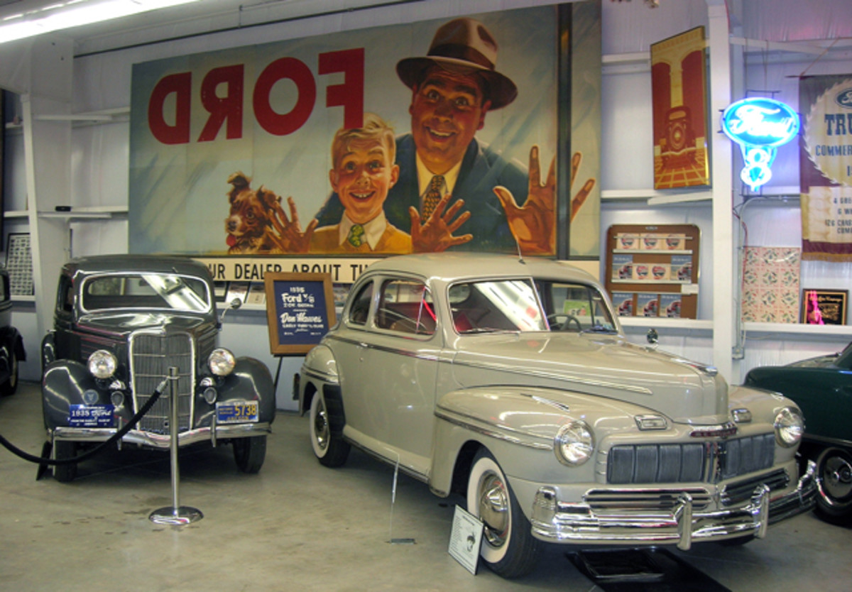 A colorful dealership display poster hovers above a 1935 Ford Tudor (left) and '46 Mercury coupe.