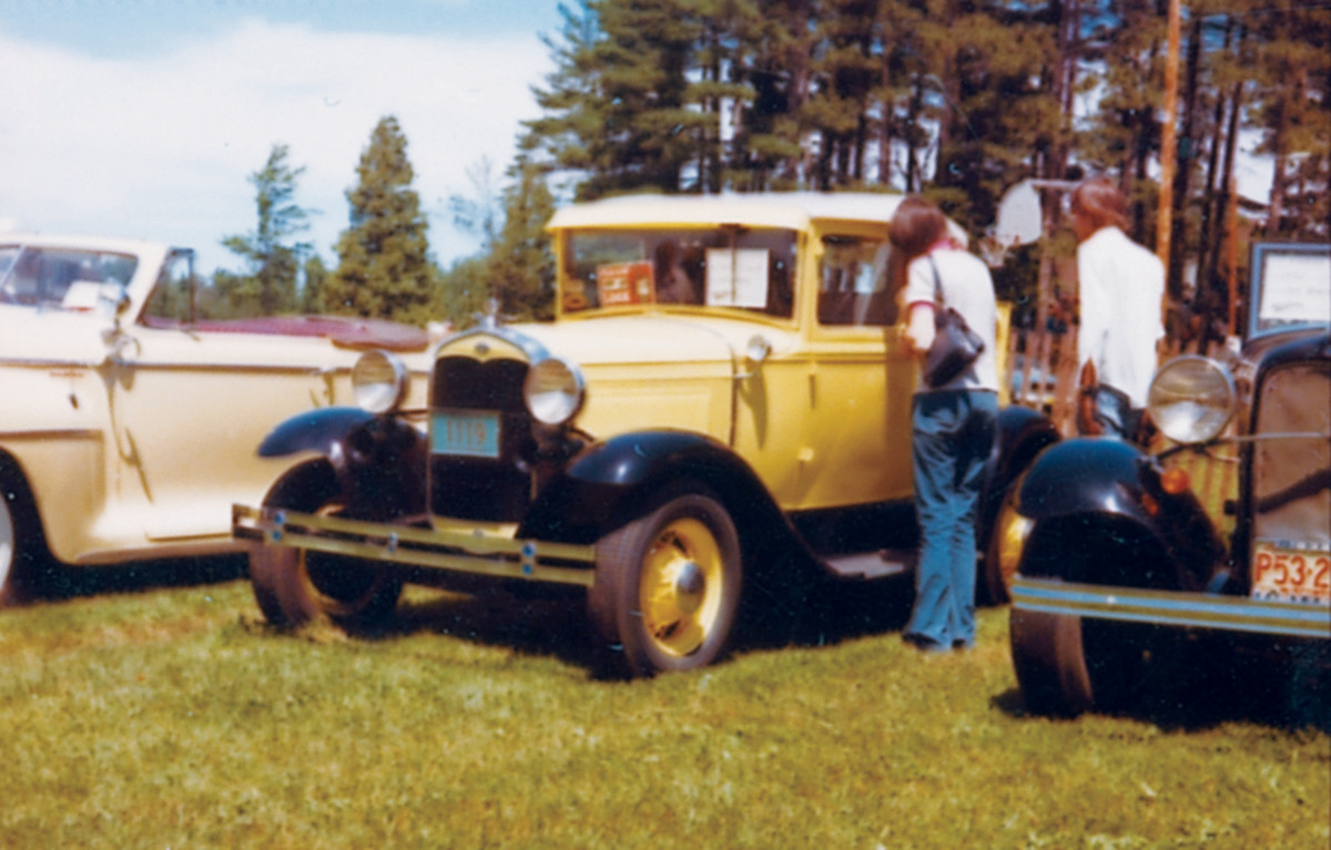 A young couple checks out a 1931 Ford Model A coupe braced by a 1932 Ford roadster and what appears to be a spotlight-equipped 1946-1948 Plymouth convertible.