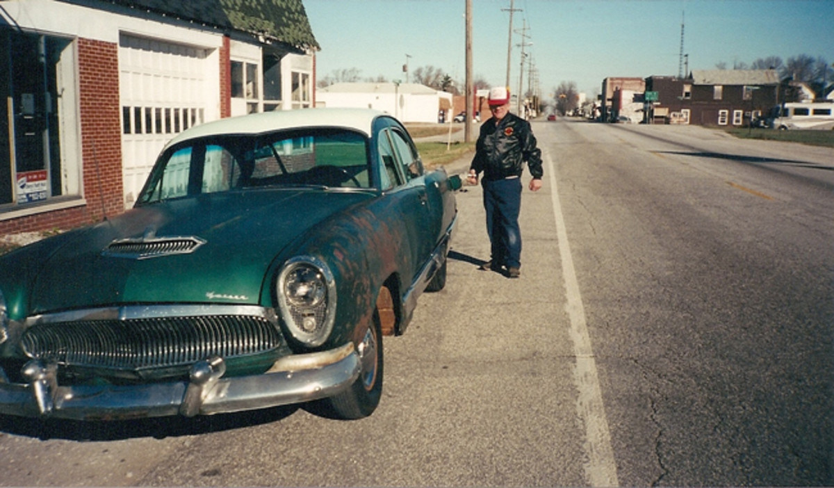 Chuck poses with the car in front of the spot that was his father's Kaiser dealership from 1946-53 in LaCrosse, Ind.