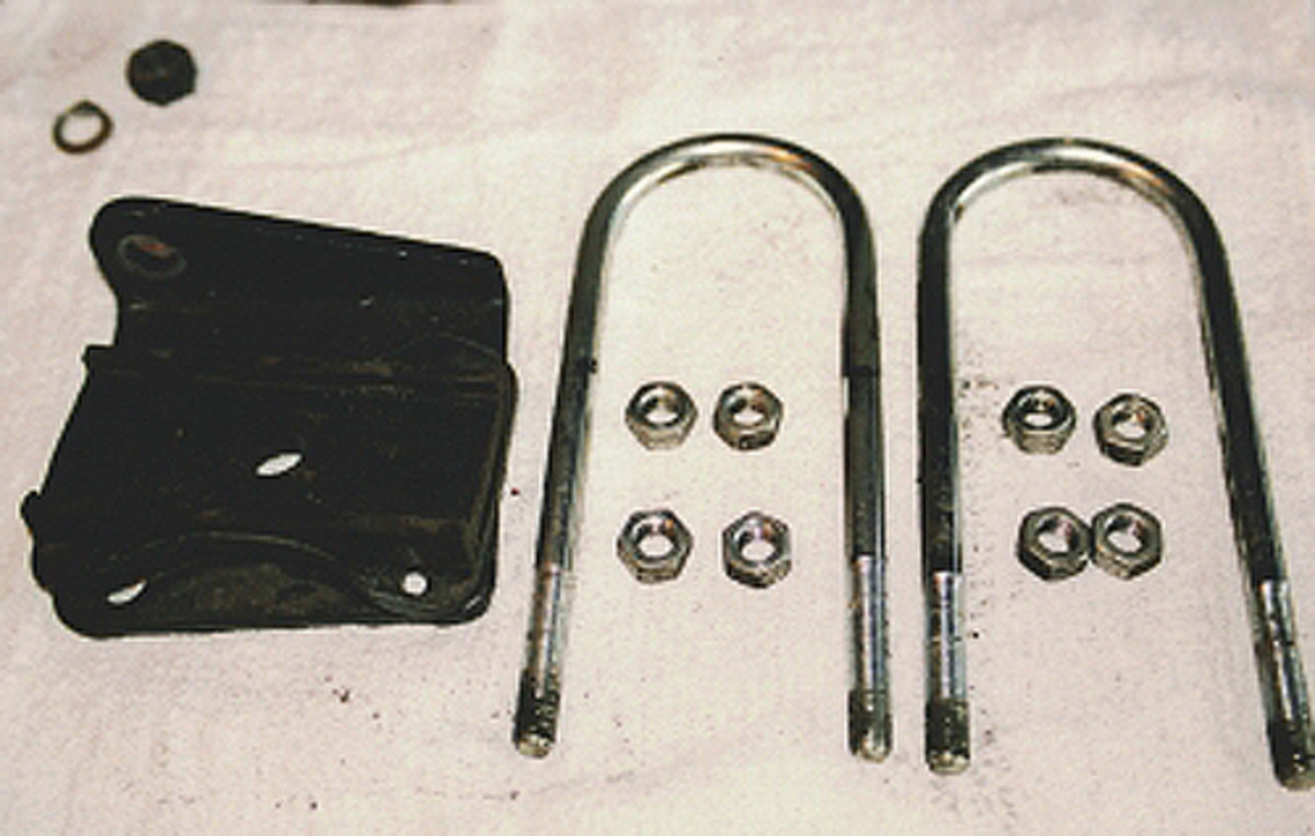 The two U-bolts hold one leaf spring on the car. The support plate bolts to the car chassis and the U-bolts go through the holes in it.