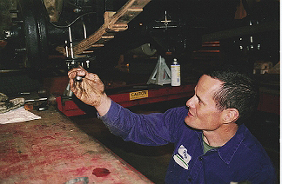 """Mechanic Vince Sauberlich loosens the nuts and locking nuts on the bottom of one of the U-bolts that holds the rear leaf springs on an MG TF. This particular """"underspung"""" car has the axle above the springs."""