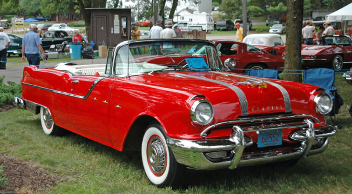 "The Clumpner family displayed their 1955 Pontiac Star Chief convertible front and center in the Blue Ribbon Concours of IOLA '14. The car, nicknamed ""Big Red,"" is accessorized with a continental kit, wire wheel covers and a front bumper guard."