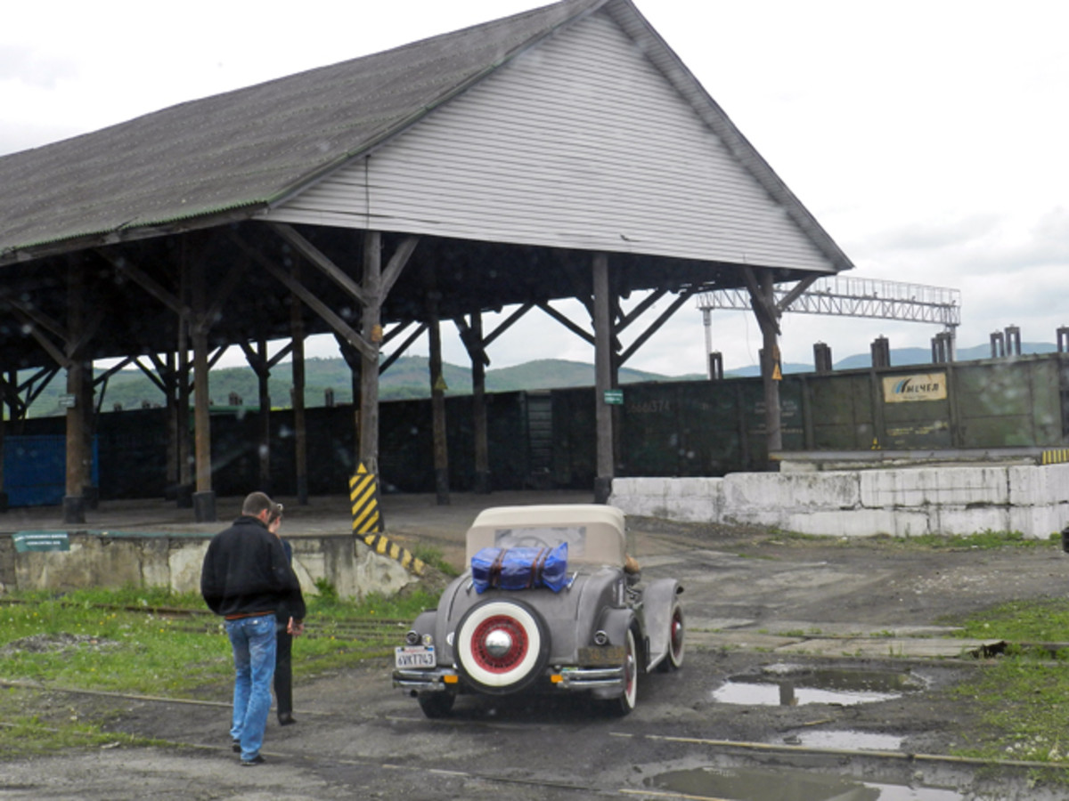 Troubles had to be overcome on the fly when John Quam was circling the globe in his 1928 Plymouth. Here, he uses a ramp at an abandoned railroad depot to load his Plymouth onto a truck in order to cross from Russia to China.