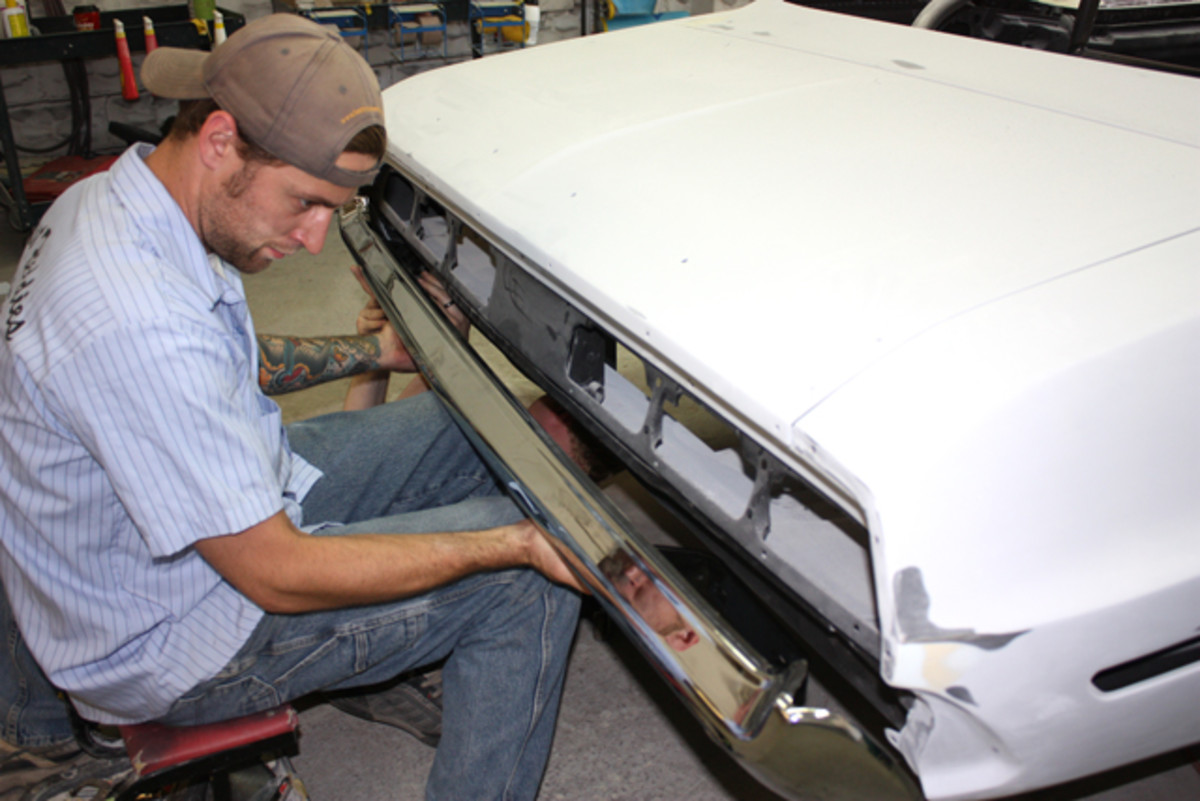 "Having an extra pair of hands definitely makes fitting a bumper easier. Here Peter Schnoor holds the bumper in place while Sean Branson bolts things up under the back of the car. ""It's always nice when you are restoring any of these cars to be able to use the original parts that were on the car,"" Schnoor noted. ""Unfortunately, this bumper was just bent up and beat up. Forty-five years of being on the road wasn't nice to it."""