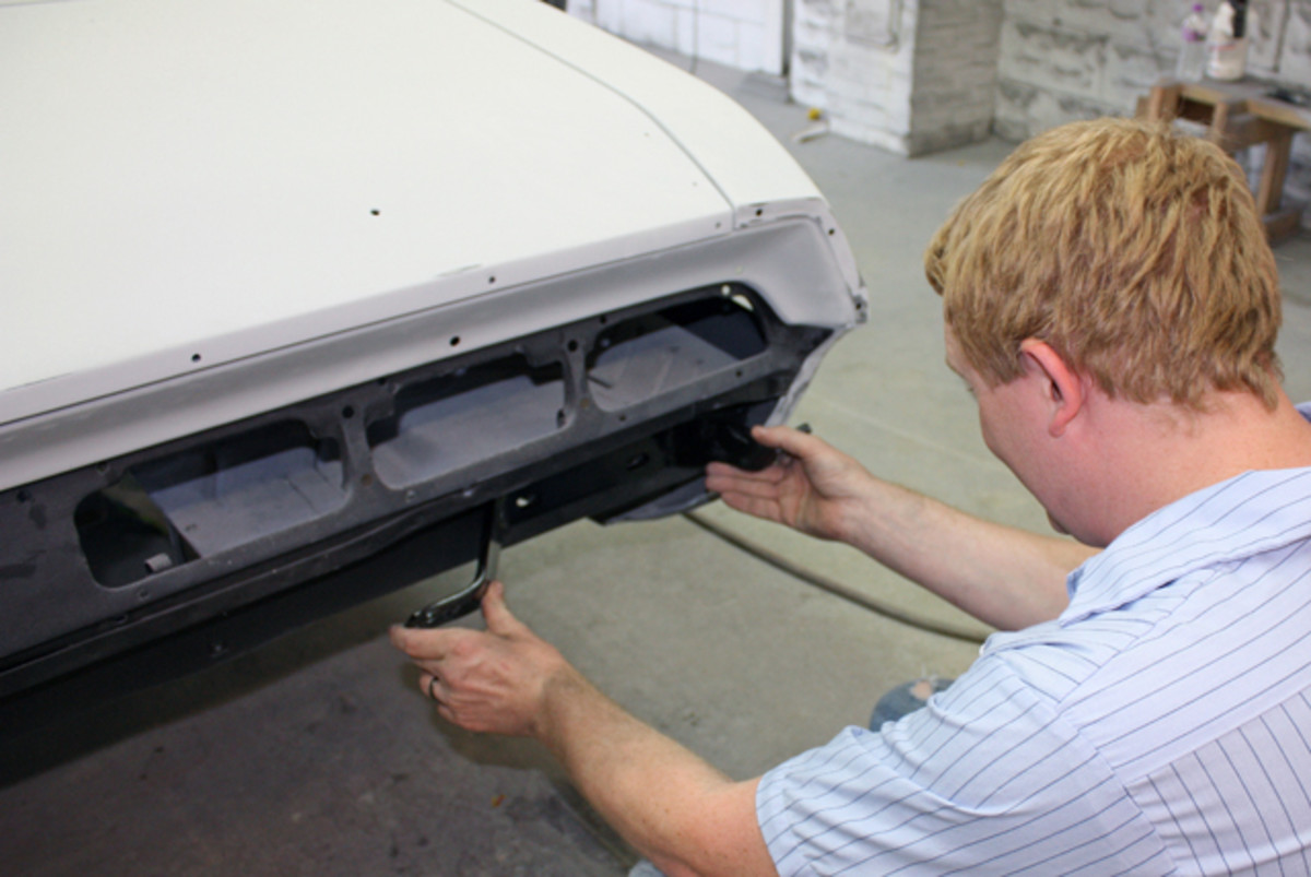 "Sean Branson eyeballs the new mounting brackets to determine if the existing holes will work. ""A lot of times you'll have to hog out some holes and maybe do a little welding on the brackets,"" he said. ""We have an aftermarket bumper and aftermarket bracket, and a lot of times you'll be just an 1/8 inch off and you'll have to adjust the holes. This gives you a lot of adjustment left to right, but not as much up and down."""