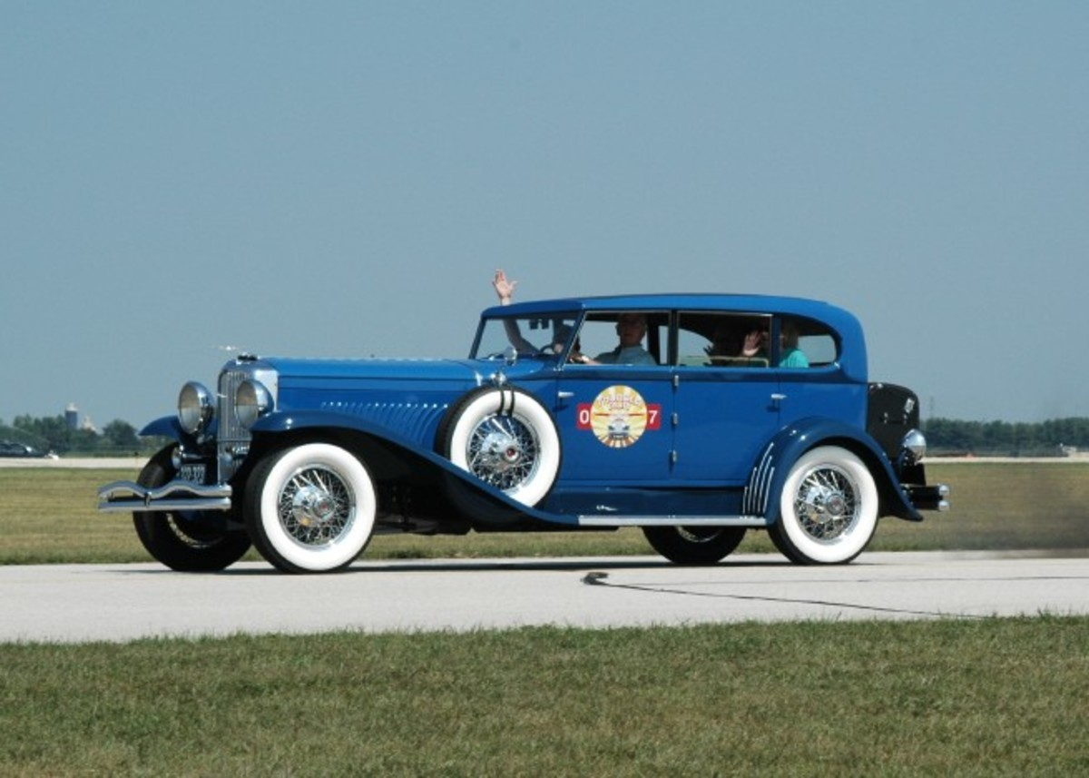 A Duesenberg Model J with Murphy Clear Vision Sedan coachwork makes a pass at the Goshen (Indiana) Municipal Airport.