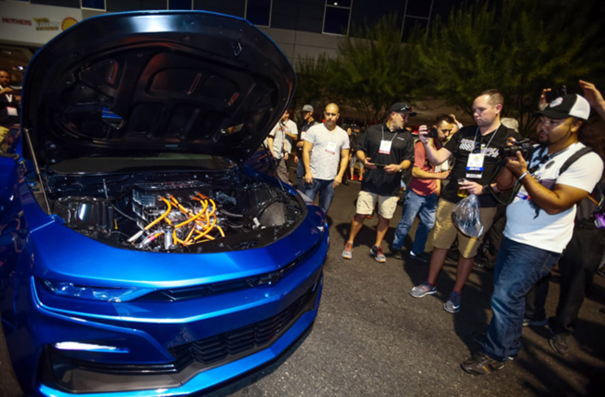 Show-goers get a closer look under the hood of the eCOPO Camaro Concept - an electrified vision for drag racing - Monday, October 29, 2018 at the SEMA Show in Las Vegas, Nevada. Developed by General Motors and built in partnership with the pioneering electric drag racing team Hancock and Lane Racing, the concept race car — based on the 2019 COPO Camaro — is entirely electric powered, driven by an electric motor providing the equivalent of more than 700 horsepower and 600 lb-ft of torque. Chevrolet estimates quarter-mile times in the 9-second range. Testing is ongoing. (Photo by Isaac Brekken for Chevrolet)
