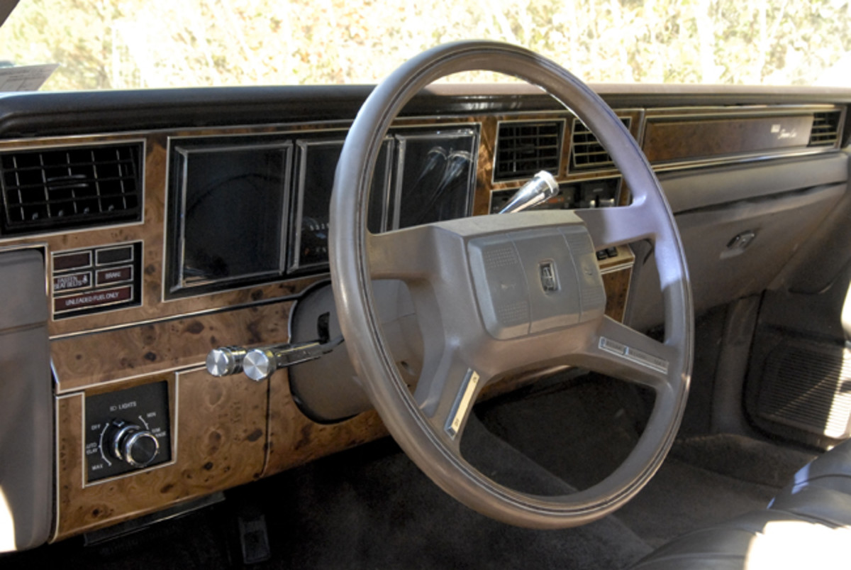 """The Town Car's instrument panel uses electronic displays and simulated woodgrain. Somewhat surprising is its lack of a """"Delray Edition"""" emblem."""