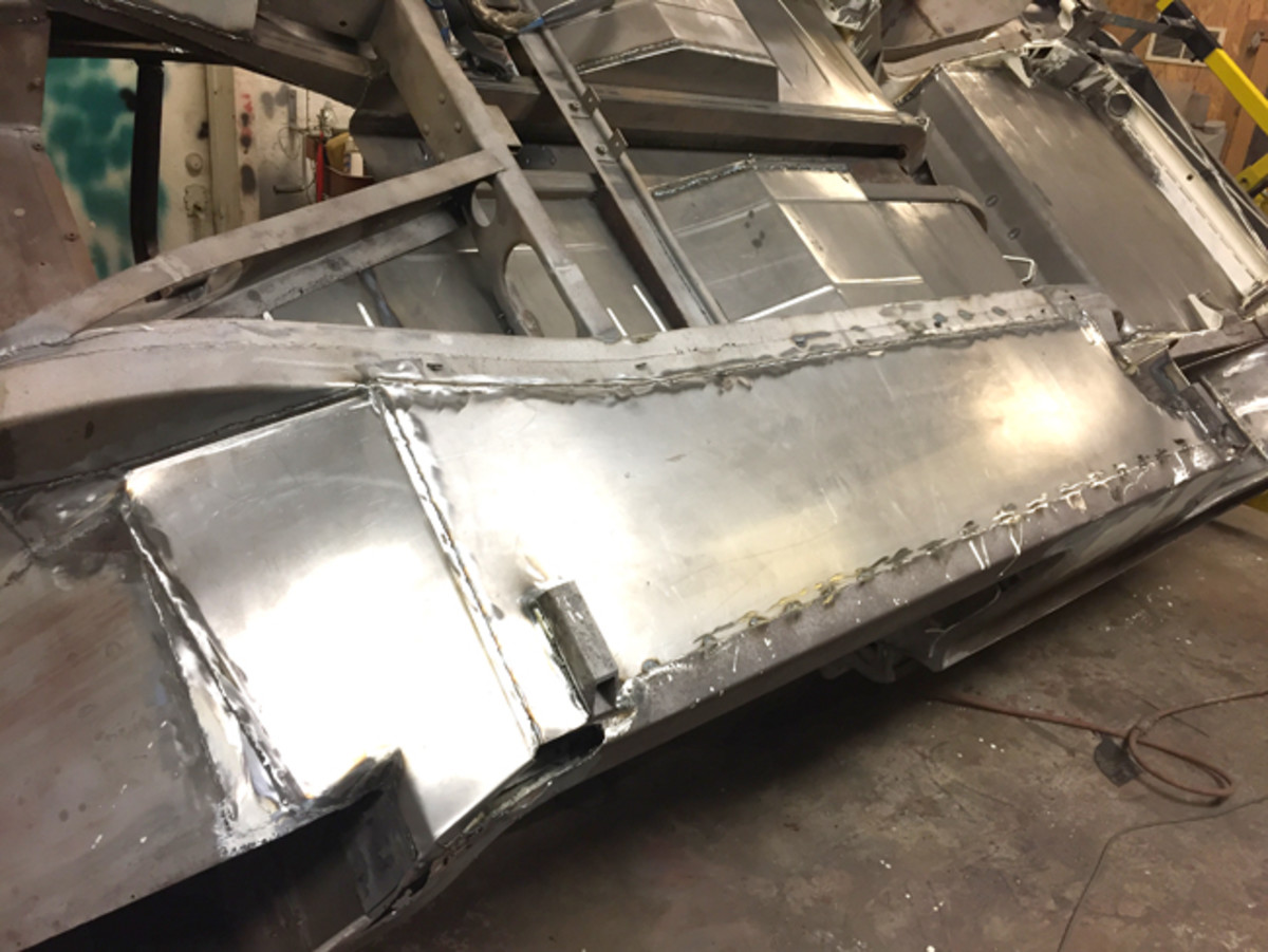 """The braces in the floor of XM-Turnpike Cruiser floor are sandwiched between the upper floor pan and a type of lower """"belly pan."""" That belly pan is pictured welded in place."""