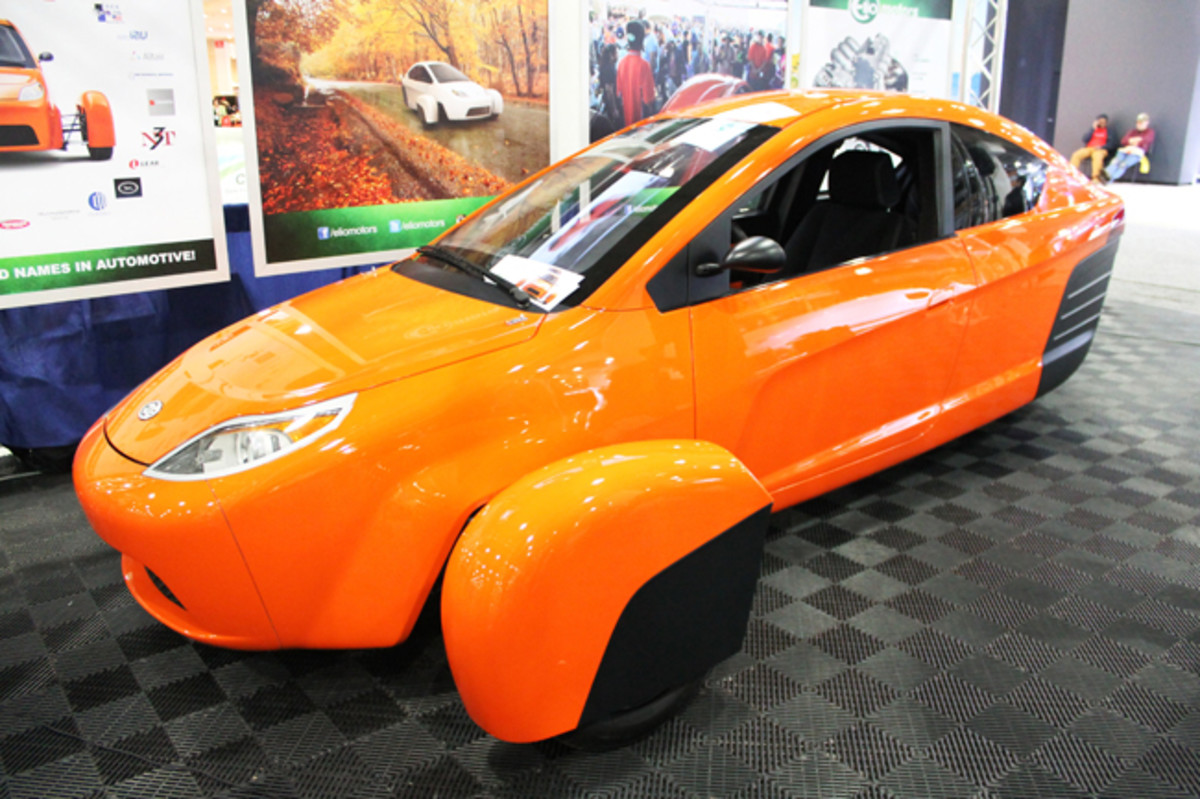 "Elio Motors has moved into GM's old Shreveport, Louisiana plant to initiate production of this 3-wheeled, 3-cylinder, front-drive city car promising 84 MPG and a $6,800 starting price. Seating the passenger behind the driver, Paul Elio explained, ""doubles the mileage because there's less car moving through the air. We've had people as big as 435 pounds and 7-foot-4 inside."" It's another plus that the cycle-style fenders are plainly visible from the driver's seat, where it's also possible to rest one's elbows on both window sills simultaneously."