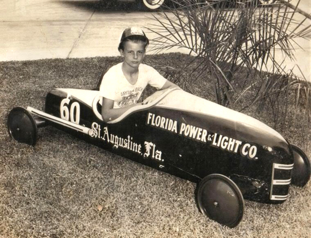 A young boy in his Soap Box Derby car. When we were kids, derby (or Chevy) representatives would come to our school to talk the race up to us kids.
