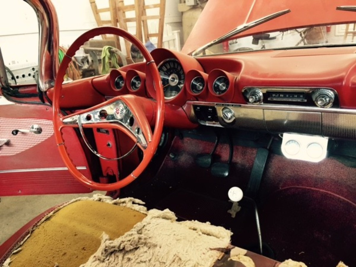 """The interior is tattered but as original as the outside. The original owner added the Stewart-Warner under-dash gauges. Also note the original """"spaghetti handle"""" four-speed shift handle."""