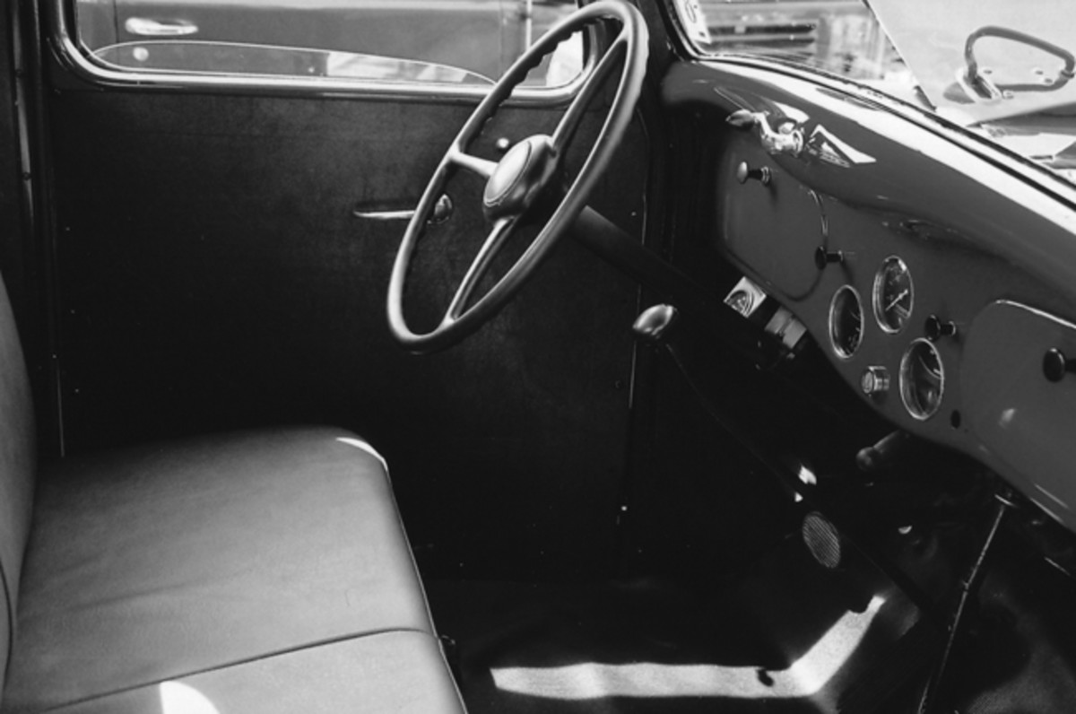 The metal dashboard has three round-faced gauges in its center, flanked by storage boxes on either side.