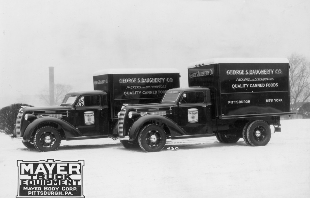 """A duo of red Diamond T Model 211 chassis for the George S. Daughterty Co., """"packers and distributors of quality canned foods"""" in Pittsburgh and New York, wear semi-deluxe panel bodies by Mayer Body Corp. The Mayer body on each 135-inch-wheelbase Diamond T was 8 feet long, 4-feet 7-inches wide and 5 feet high on the inside with a French-type round-edged roof design to match the sleek look of the stylish Diamond T cab. Like the cab, the body of each was well appointed with a rear end gate, screened safety glass lookout window at the front and a dome light inside the body."""
