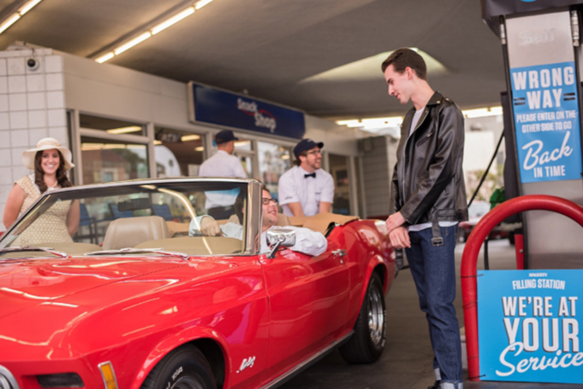 Jason Perls Miller, 28, of Culver City, CA with his 1970 Ford Mustang Convertible purchased gas for 35 cents a gallon during the Hagerty vintage gas station event celebrating National Collector Car Appreciation Day. (PRNewsFoto/Hagerty)