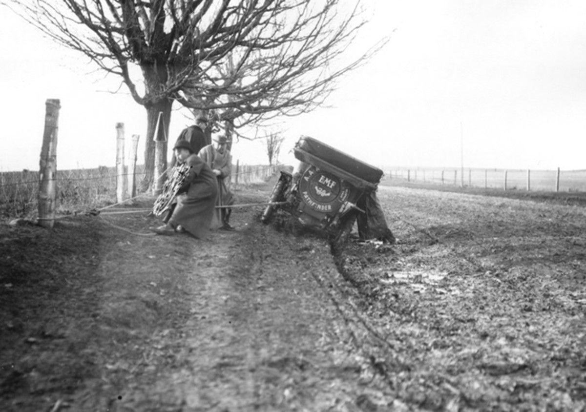 """This photo shows an EMF 30 Touring Car, outfitted with tire chains, and four men working with ropes, attempting to get it unstuck from a typical muddy road, circa 1909. Historian Jim Craft will speak at the Museum about """"The Good Roads Movement,"""" which was championed not by motorist but by bicyclist in the late 1880s.Photo: Gilmore Car Museum"""