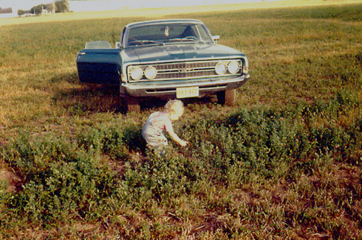 The '68 Torino keeps watch over me as a toddler. I have no idea why it is parked in the hay field.