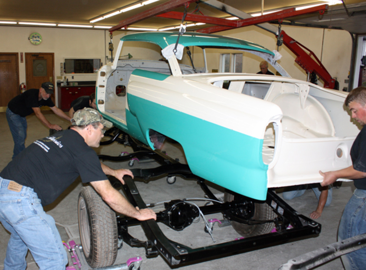 This 1956 Mercury hardtop has been completely torn down. One of the first steps in the re-assembly is dropping the shiny, freshly painted body shell on the equally shiny frame. The next step will be to hang the doors.