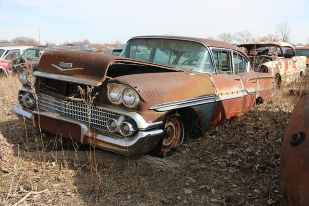 This 1958 Chevrolet Biscayne four-door came from the factory with a V-8 engine. It is still under the hood, but several engine parts have been removed. The trim has been completely stripped from the 1956 Olds Holiday coupe behind it.
