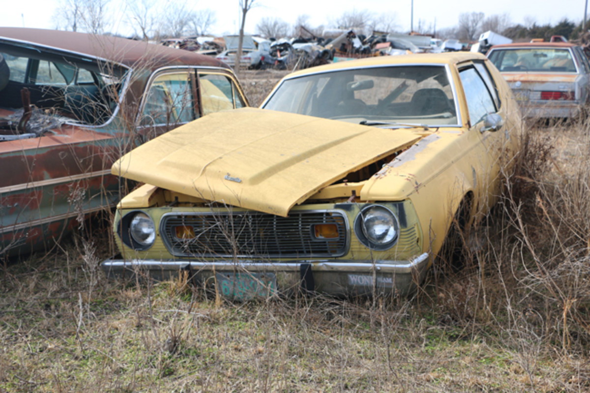 A bright-yellow AMC Gremlin with a loose hood is available for parts.