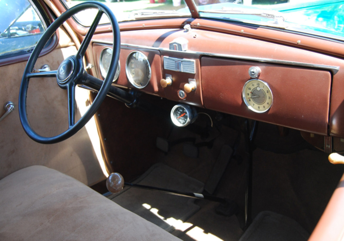 Though advertised as a five-passenger car, the Pontiac interior dimensions are a tight fit for 6-footers, On coaches the front seat backs fold forward for rear passenger entry. The 1936 dashboard layout is pretty simple. The translucent knobs were used on Deluxe models. Knob below windshield division bar operates the vacuum wipers.
