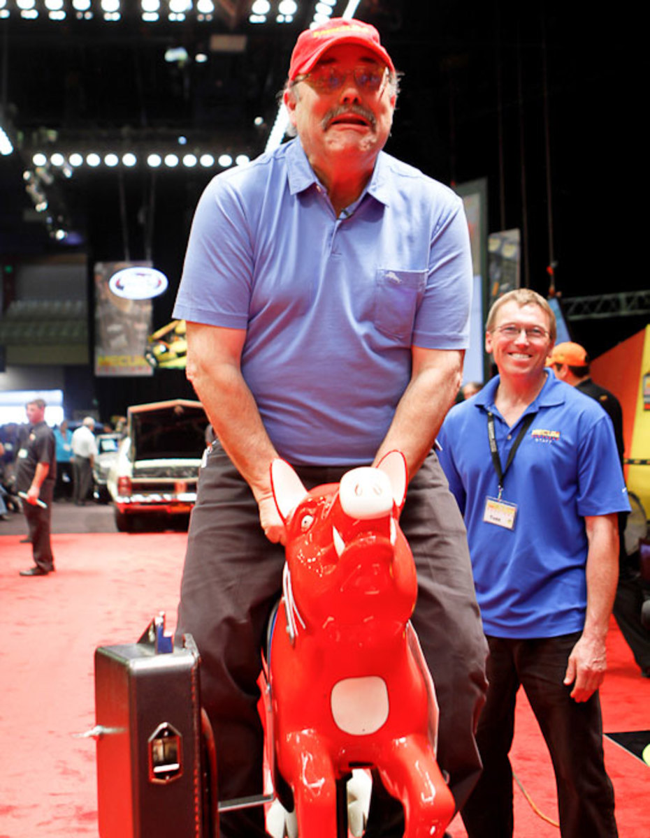 You never know what will happen at a Mecum Auction, here Dana Mecum tests out a kiddie ride to the delight of everyone on hand. (Courtesy of Philip Podskalan)