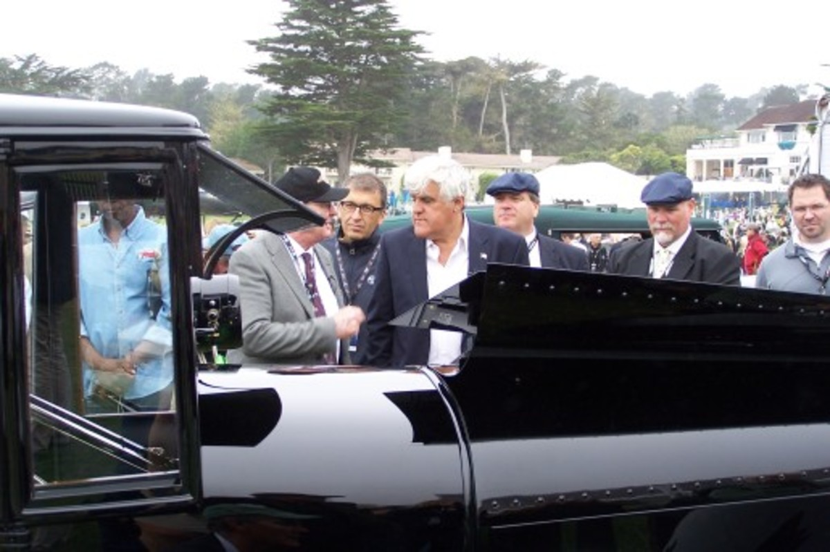 Jay Leno is given a tour of the Duesenberg Model A Bender coupe during the 2013 Pebble Beach Concours d'Elegance.