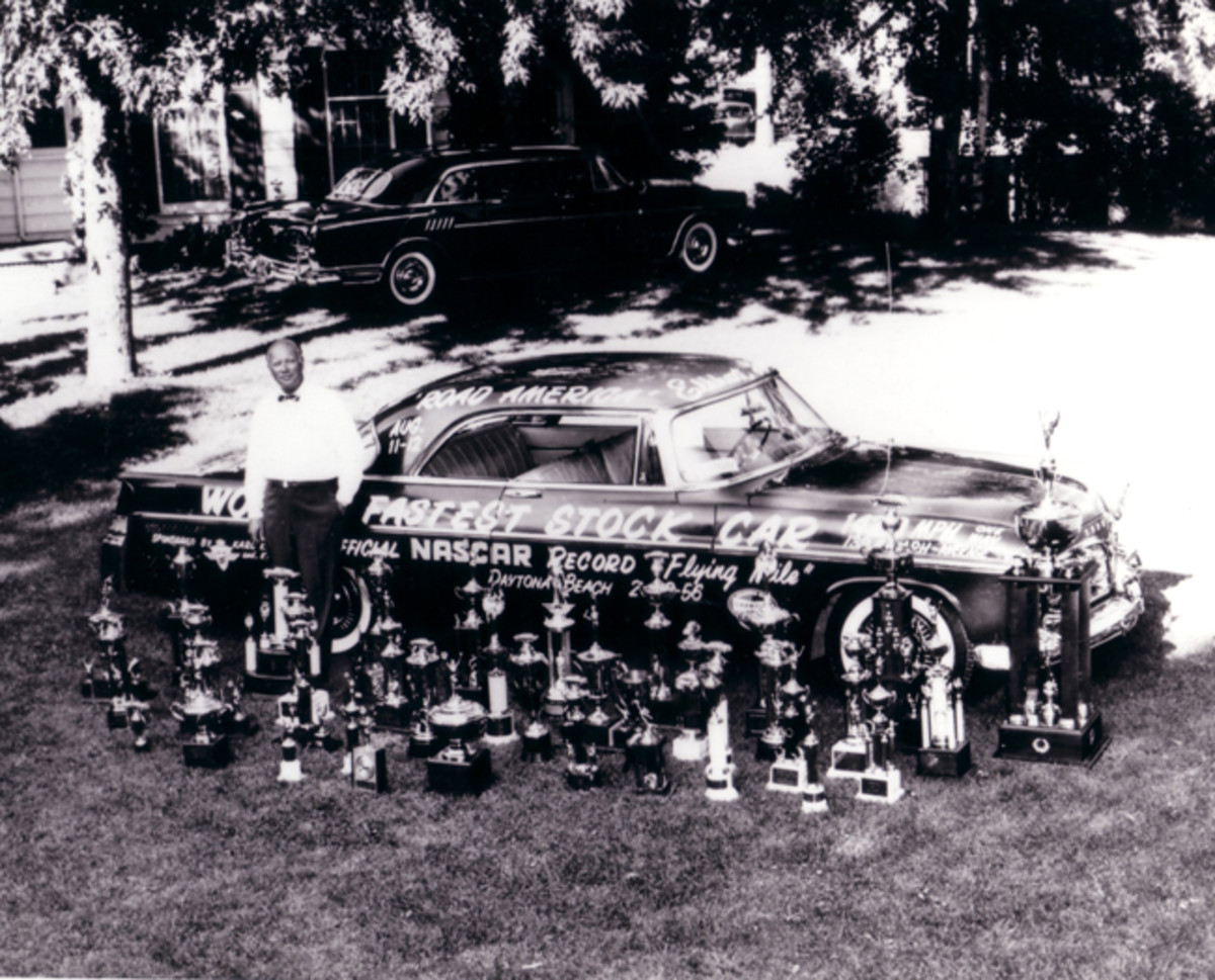 Mike Martin's boss Carl Kiekaefer with one of his famous Chrysler 300 racing cars and a bunch of trophies the racing cars won.
