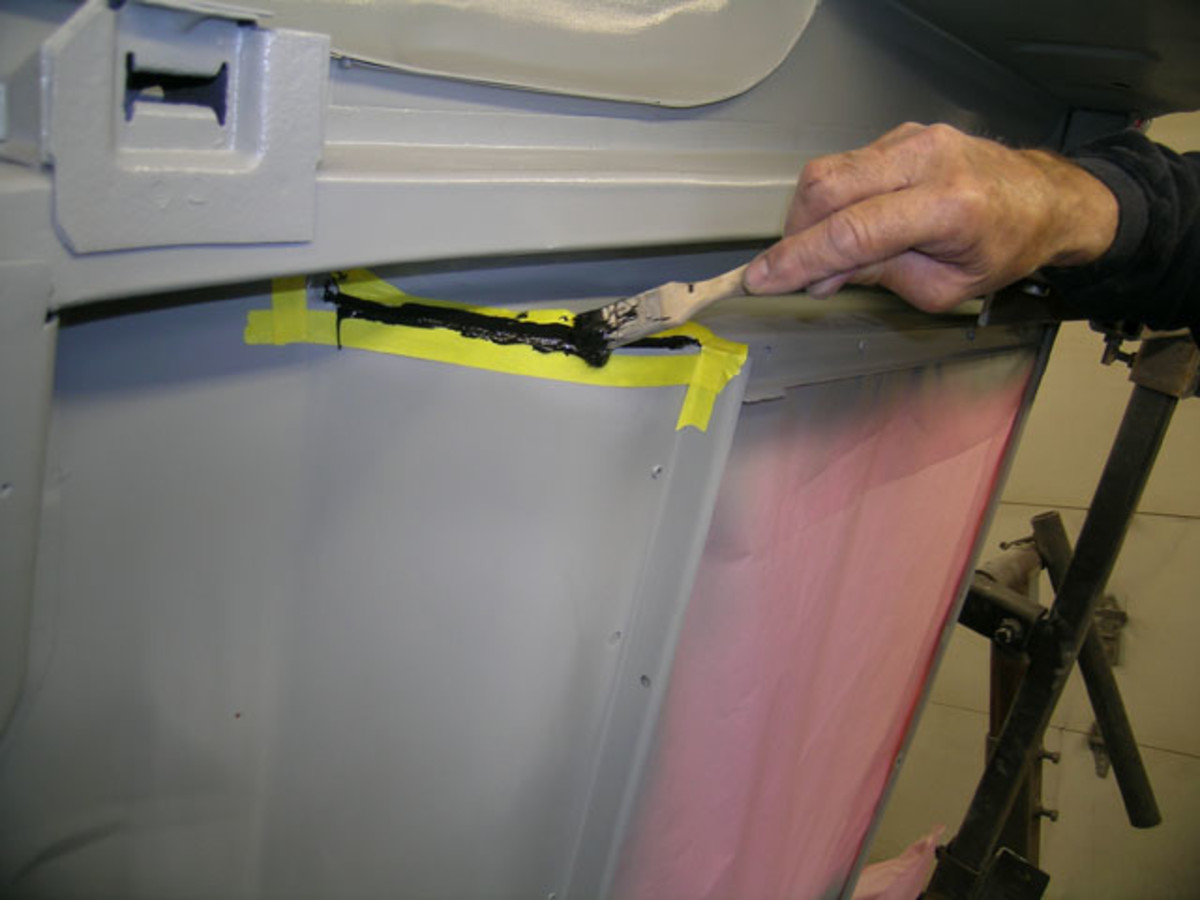 Spreading the seam sealer with a brush. Note tape on each side of the seam to direct its application. While the seam sealer is wet, the tape will be peeled off to create a straight edge.