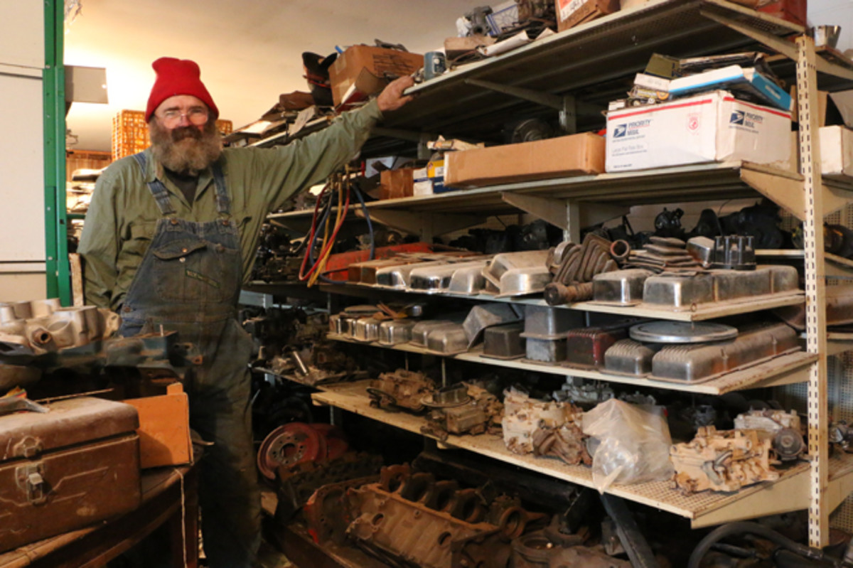 Randall Watts poses by shelves loaded with used parts such as intake manifolds, carburetors, valve covers plus much more.