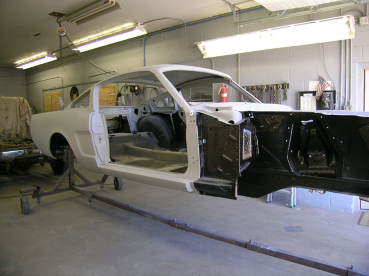 The Mustang body ready for paint. Notice where the black bedliner material was sprayed; the areas of gray epoxy sealer will receive body-color paint.