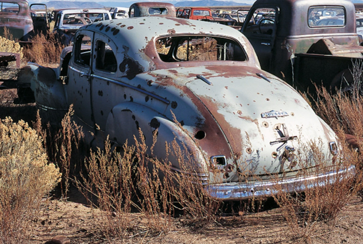 Prior to being parked in the yard, someone with a shotgun used this 1947 Hudson Commodore coupe as target practice. Beyond the prevalent bullet holes, the car's body panels remain solid.