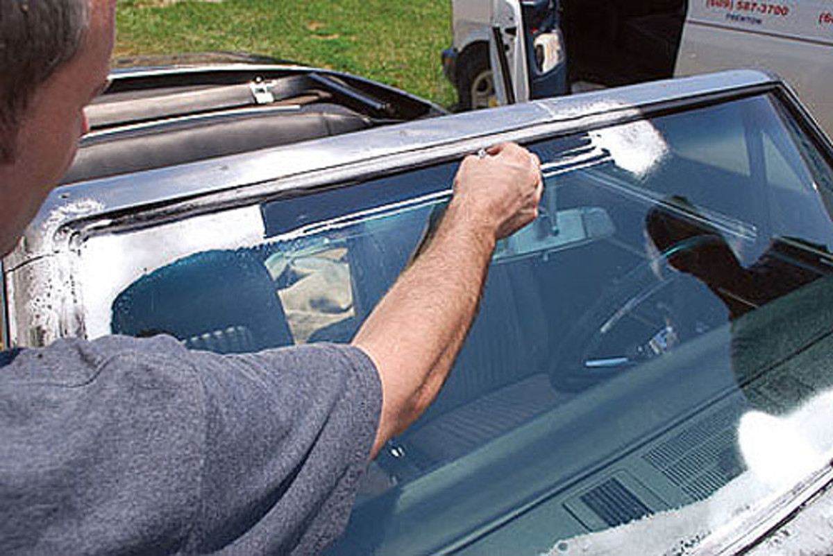 Once the trim is in, some of the sealer gets pushed out onto the glass. Brian uses a spray window cleaner as a lubricant and scrapes the sealer off the windshield with a razor blade, kind of like shaving. The spray helps keep cleanup to a minimum.