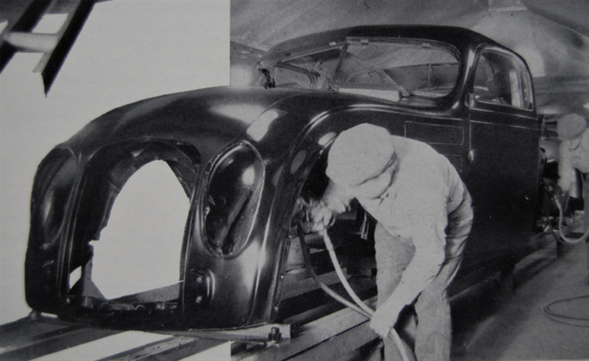 A painter sprays the inside fenders of a unit-bodied Airflow model.