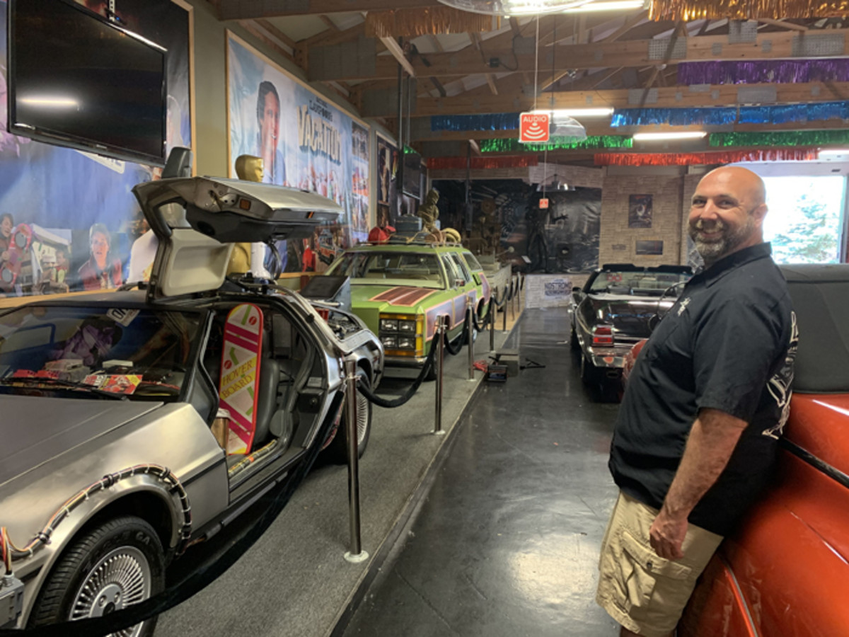 """The family truckster from """"National Lampoon's Vacation"""" is seen in the background as Volo Auto Museum Director Brian Grams talks about new exhibit installations and other work under way at the Volo Auto Museum while it is closed. The Grams family has elected not to reopen the museum under current Phase 4 restrictions."""